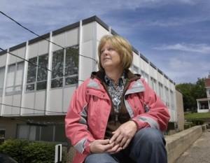 Mary sentada na calçada em frente à clinica de aborto. Atrás dela está o prédio da Heritage Clinic para Mulheres (a clínica de aborto)